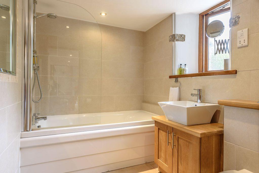 Ground floor house bathroom with whirlpool bath and shower over